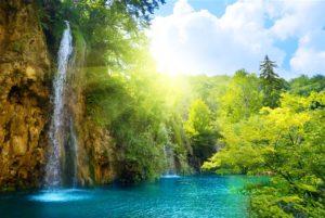 陽光下的美麗小溪瀑布攝影圖片